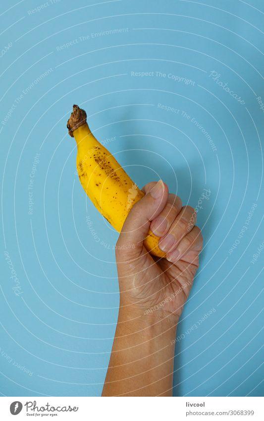 Banane auf blauer Wand II Lebensmittel Gemüse Frucht Ernährung Lifestyle Design Mensch Frau Erwachsene Arme Hand Finger Natur genießen frisch Gesundheit lecker