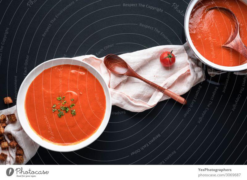 Tomatensuppe auf schwarzem Tisch. Gesunde hausgemachte Suppe Gemüse Eintopf Kräuter & Gewürze Ernährung Mittagessen Abendessen Vegetarische Ernährung Diät