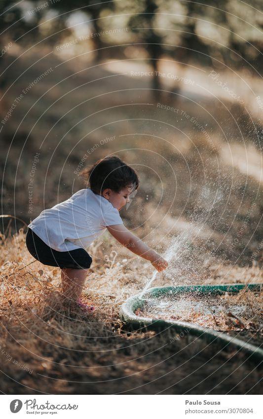 Kind spielt mit dem Wasserschlauch Lifestyle Mensch Kleinkind Mädchen 1 1-3 Jahre Sommer berühren genießen Spielen Fröhlichkeit Glück lustig Neugier wild