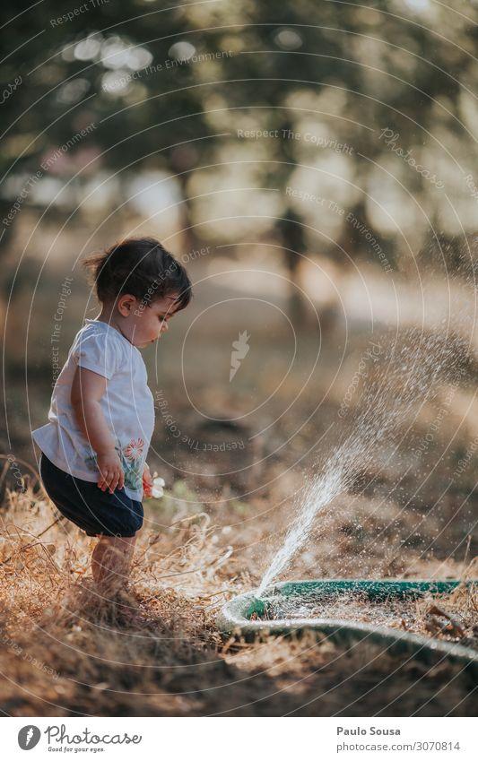 Kleines Mädchen steht bereit, wenn Wasser aus einem Schlauch an Land spritzt Kind Kindheit Sommer Sommerurlaub Sommertag Außenaufnahme Farbfoto sommerlich Natur