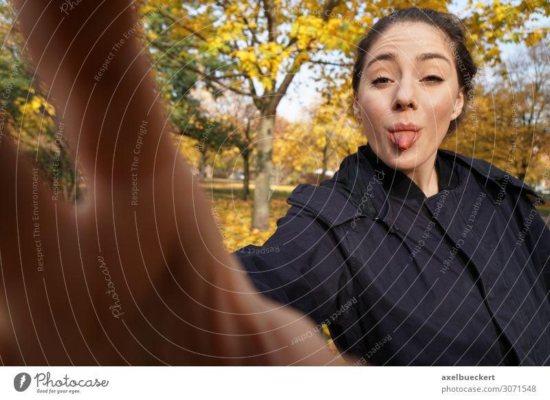 junge Frau steckt Kamera die Zunge raus Mensch Jugendliche Junge Frau Hand Freude 18-30 Jahre Lifestyle Erwachsene Herbst lustig außergewöhnlich