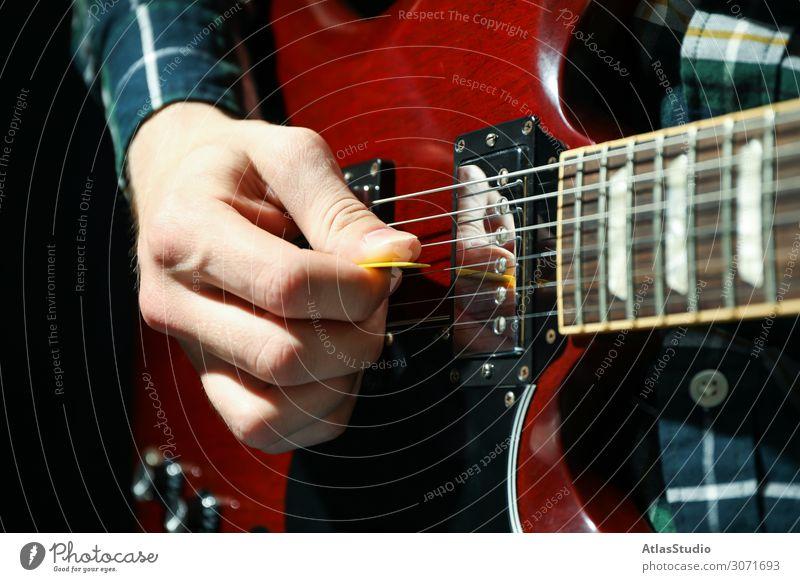 Mann spielt auf E-Gitarre vor dunklem Hintergrund, Nahaufnahme Instrument Lichtschein schließen live pflücken Musiker jung Tisch Raum spielen Blues Gesang solo