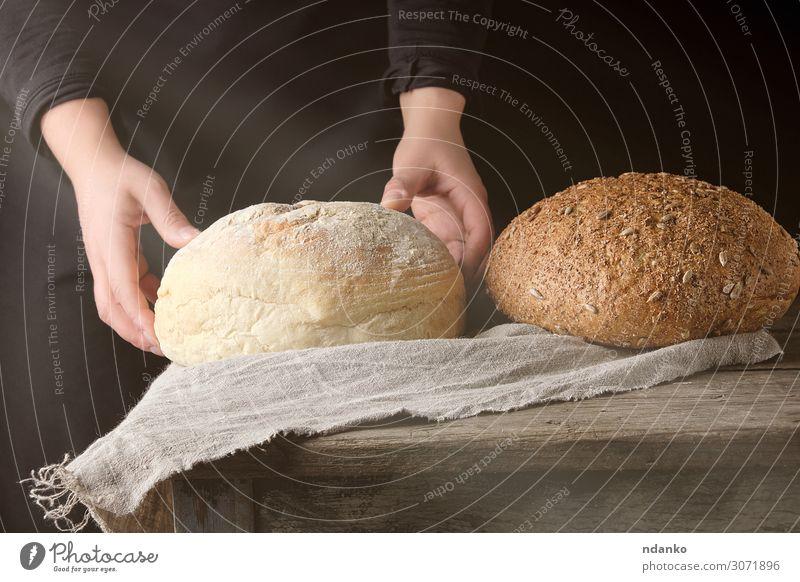zwei weibliche Hände lagen auf einem Tisch, der mit weißem Rundbrot gebacken wurde. Teigwaren Backwaren Brot Frühstück Sonne Küche Mensch Frau Erwachsene Arme