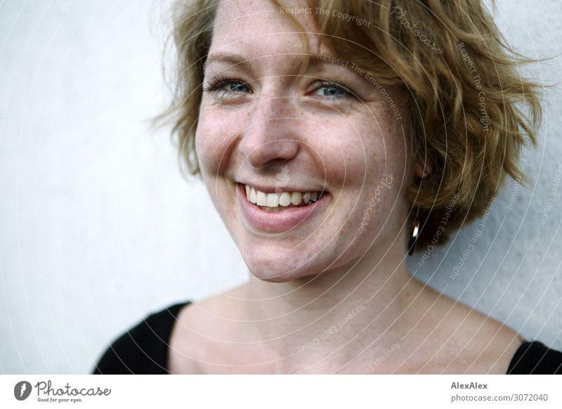 Junge Frau vor weißer Wand lächelt Lifestyle Freude Glück schön Wohlgefühl Jugendliche Gesicht Sommersprossen 18-30 Jahre Erwachsene Top Ohrringe brünett