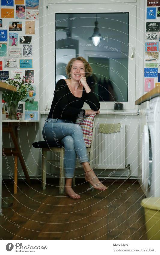 Junge Frau sitzt in ihrer Küche - Portrait Jugendliche Stadt schön Freude Fenster 18-30 Jahre Lifestyle Erwachsene natürlich feminin lachen