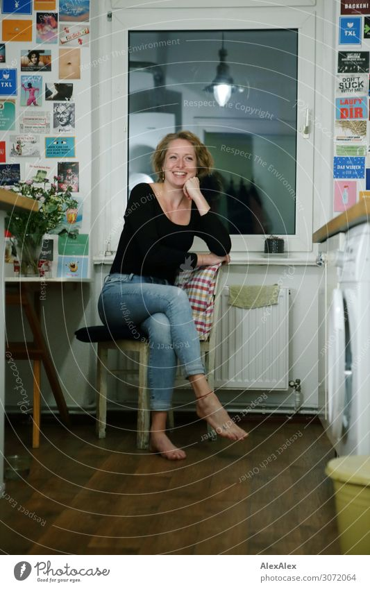 Junge Frau sitzt seitlich auf einem Stuhll in ihrer Küche und lächelt - Studentin Lifestyle Freude schön Wohlgefühl Dekoration & Verzierung Tisch Fenster
