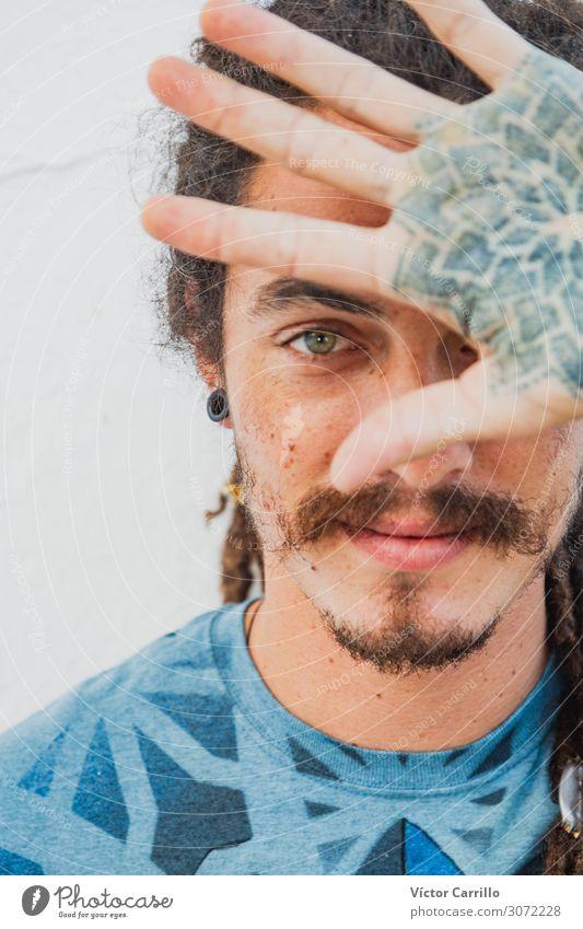 Ein bemalter junger Mann mit grünen Augen. Lifestyle Freude Glück schön Erholung Tourismus Sommer Strand Frau Erwachsene Freundschaft Jugendliche Fröhlichkeit