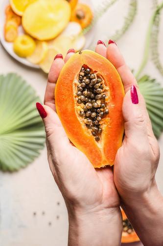 Frauenhände halten halbe Papaya mit Kerne Gesunde Ernährung Hand Foodfotografie Lebensmittel Essen Erwachsene Frucht Design Frühstück Bioprodukte