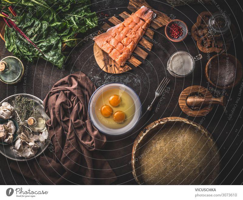 Quiche-Zutaten oder offener Kuchen: Lachs, Mangold, Eier, Sahne, Teig in Backform auf dunklem, rustikalem Tischhintergrund mit Küchenutensilien, Draufsicht. Zubereitung der Speisen