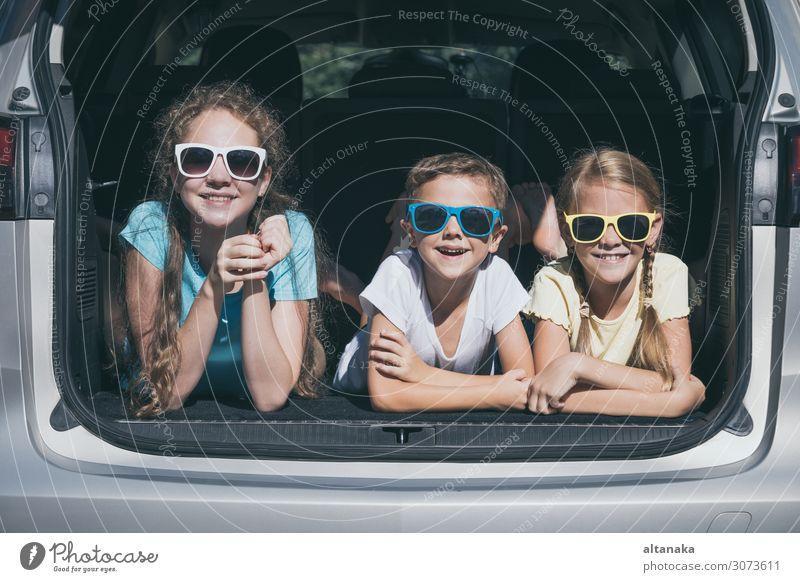 Der glückliche Bruder und seine beiden Schwestern sitzen zur Tageszeit im Auto. Kinder haben Spaß im Freien. Das Konzept der Familie ist reisefertig. Lifestyle