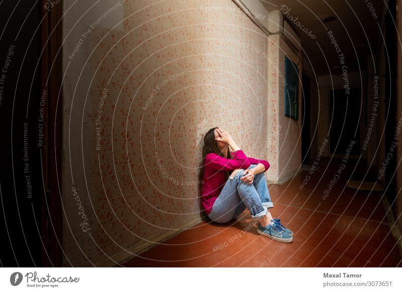 Traurige und verzweifelte Frau sitzt in einem dunklen Korridor. Erwachsene sitzen Traurigkeit dunkel Gefühle Sorge Trauer Einsamkeit Fürsorge Verlassenwerden