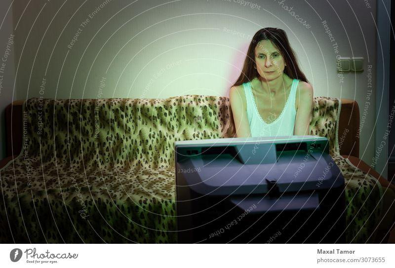 Eine Frau mittleren Alters, allein, schaut fern. Lifestyle Gesicht Erholung Freizeit & Hobby Sofa Publikum Fernseher Bildschirm Mensch Erwachsene Medien