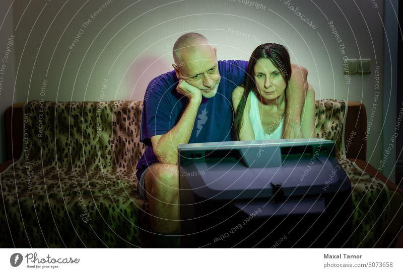 Ein paar erwachsene Liebhaber schauen sich einen Film im Fernsehen an. Lifestyle Erholung Freizeit & Hobby Sofa Entertainment Publikum Bildschirm Mensch Frau