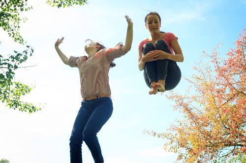 Zwei Mädchen hüpfen auf dem Trampolin, in der Natur. Leben Sinnesorgane Freizeit & Hobby Spielen Ferien & Urlaub & Reisen Sommer Sport Fitness Sport-Training