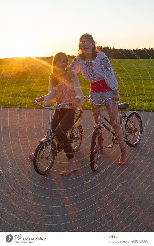 Zwei Mädchen auf Fahrrad, in der Natur bei Sonnenuntergang. Ferien & Urlaub & Reisen Ausflug Abenteuer Ferne Freiheit Freude Glück Fröhlichkeit Zufriedenheit