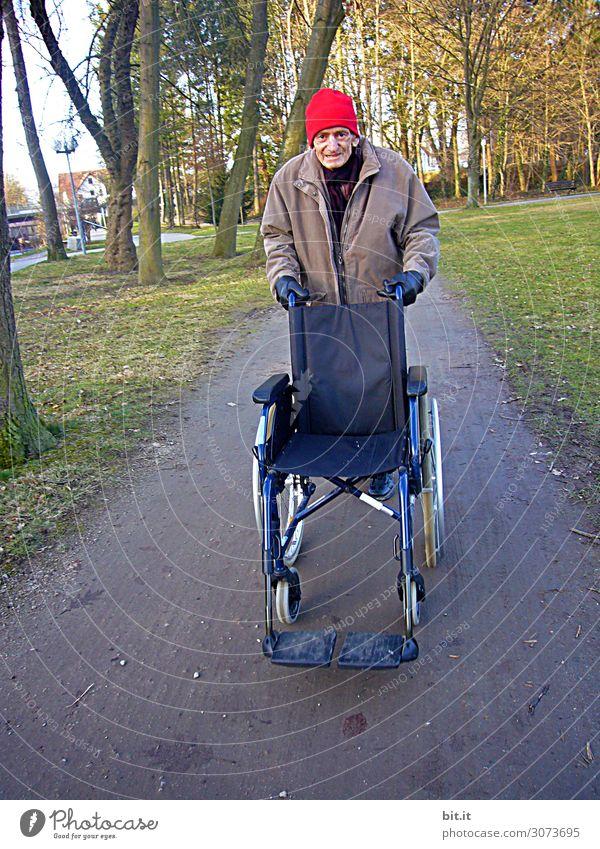 Mann schiebt Rollstuhl, auf der Straße im Wald. Mensch Erwachsene Senior maskulin Armut Männlicher Senior Großvater