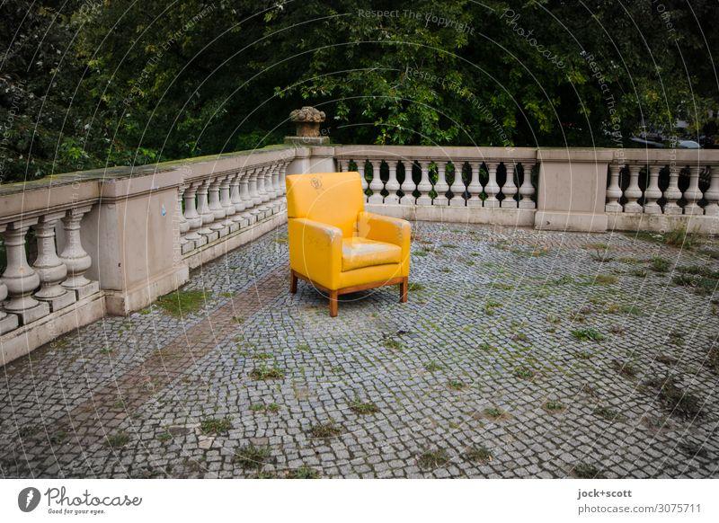 Fallen lassen auf verlorenen Polstersessel lost places Umwelt Laubbaum Neukölln Terrasse Geländer Steinboden Pflastersteine Sessel eckig frei trashig gelb