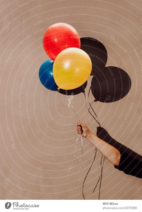 Handgehaltene bunte Luftballons Halt Farbe mehrfarbig Schatten Party rot gelb blau