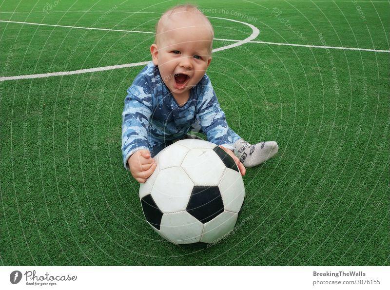 Kleiner Junge sitzt auf grünem Gras des Spielfeldes mit Fußball Fußball und Blick auf die Kamera Lifestyle Freizeit & Hobby Sport Ball Fußballplatz Stadion