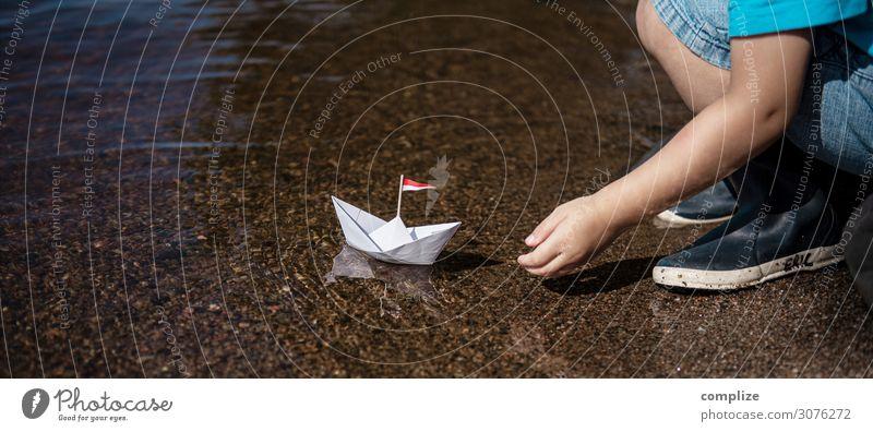 Kleiner Junge setzt kleines Papierschiff ins Wasser Kind Ferien & Urlaub & Reisen Hand Sonne Erholung ruhig Freude Strand Gesundheit Küste Glück Tourismus