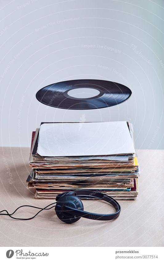 Schwarzes Vinyl hing in der Luft über einem Stapel von Vinyls. Lifestyle Stil Entertainment Musik Technik & Technologie Kultur Jugendkultur Subkultur