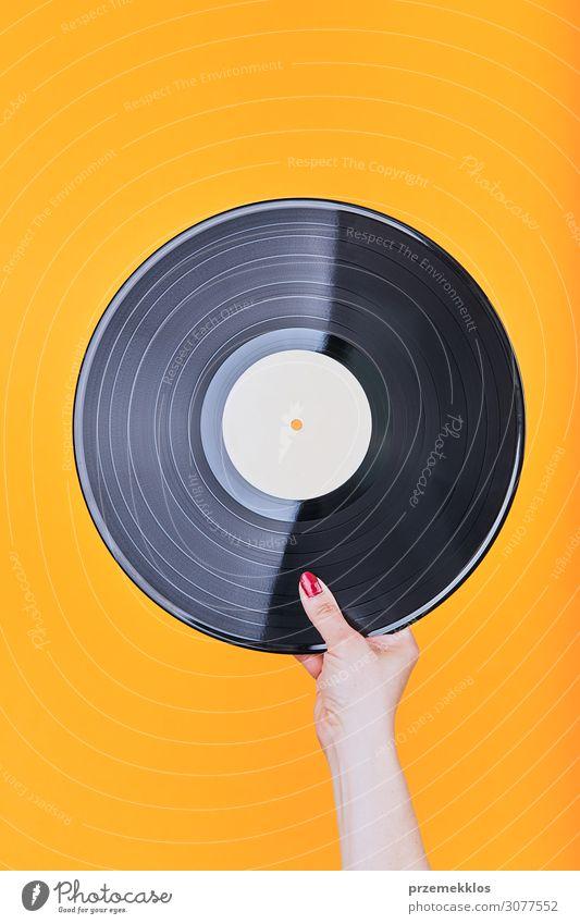 Vinylplatte über einem einfachen orangefarbenen Hintergrund Lifestyle Stil Spielen Entertainment Musik Technik & Technologie Musik hören Schallplatte Medien