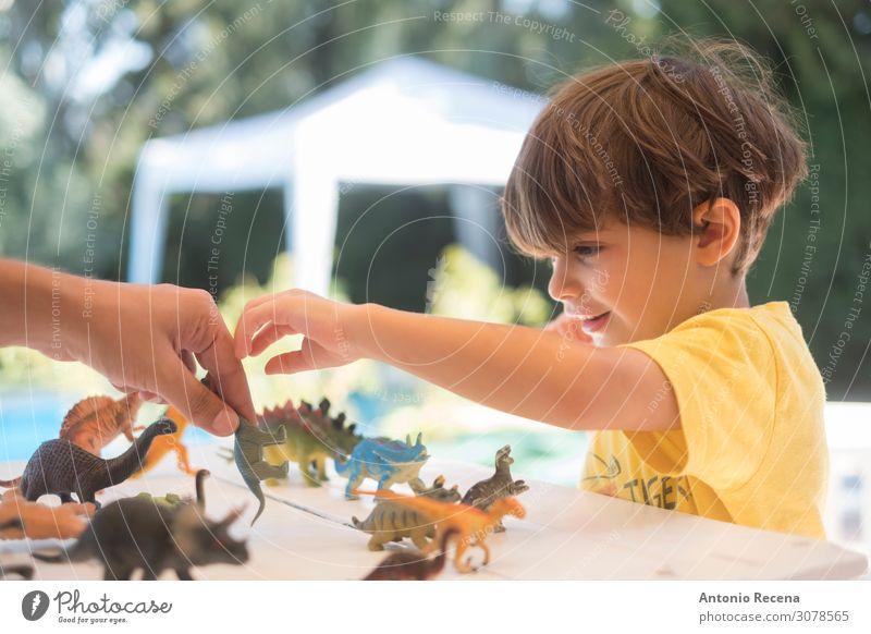 Spielzeug-Dinosaurier auf dem Tisch, Spielen Sommer Garten Kind Schule Junge Mann Erwachsene Eltern Mutter Kindheit Hand Bikini Kunststoff genießen Lächeln