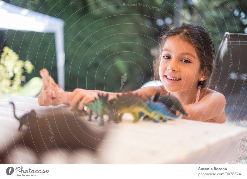 kleines Mädchen spielt mit Dinosauriern im Hausgarten Spielen Sommer Garten Kind Schule Frau Erwachsene Kindheit Bikini Spielzeug Kunststoff sitzen Badeanzug