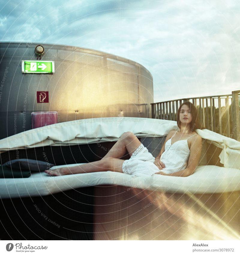 Junge Frau auf Sofa einer Dachterrasse, Lightleaks elegant Stil Freude schön harmonisch Sommer Geländer Nachtleben Jugendliche Beine 18-30 Jahre Erwachsene
