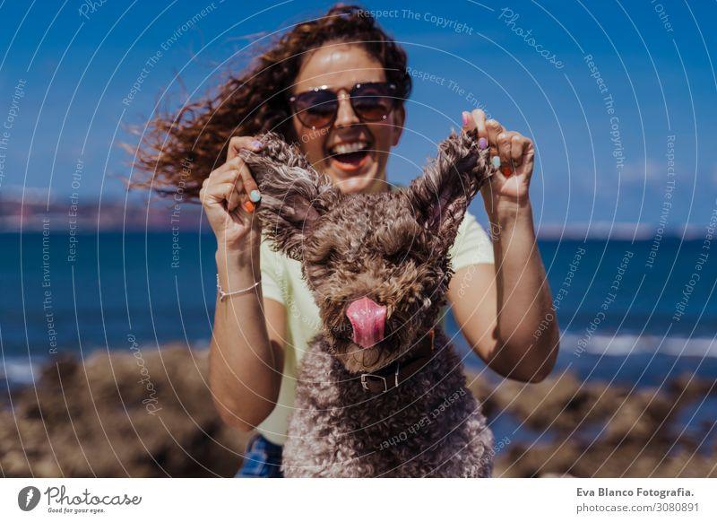 junge Frau und ihr süßer spanischer Wasserhund im Freien, die gemeinsam an einem sonnigen und windigen Tag genießen. Sommerzeit, Tierliebe und Ferienkonzept