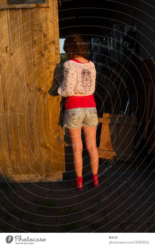 Junge Frau schaut in einen dunklen Stall. Mensch feminin Mädchen Jugendliche Kindheit Haus Hütte Gebäude Tür Blick stehen träumen dunkel schwarz Gefühle