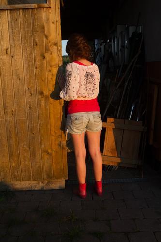 Junge Frau schaut in einen dunklen Stall. Mensch Jugendliche Haus Einsamkeit Mädchen dunkel schwarz Traurigkeit feminin Gefühle Gebäude Stimmung Angst träumen