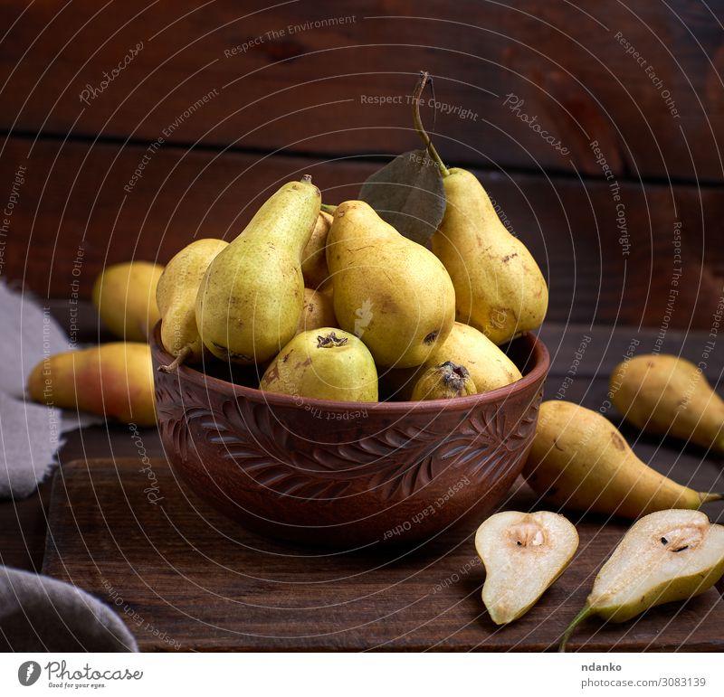frische reife grüne Birnen in einer braunen Tonschale auf einem Tisch Frucht Ernährung Vegetarische Ernährung Diät Teller Schalen & Schüsseln Natur Herbst Holz