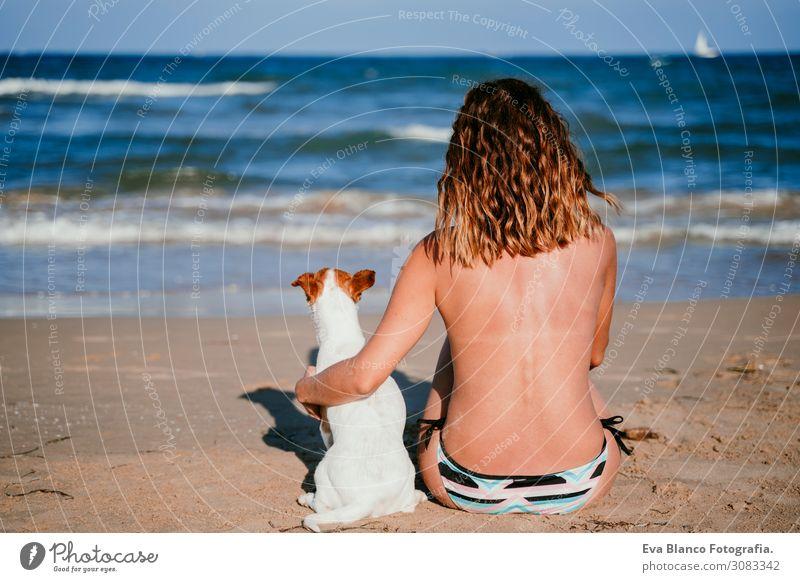 junge Frau und ihr süßer kleiner Jack-Russell-Terrier, die am Strand sitzen und sich entspannen. Sommer- und Ferienkonzept Jugendliche Erholung blau Erwachsene