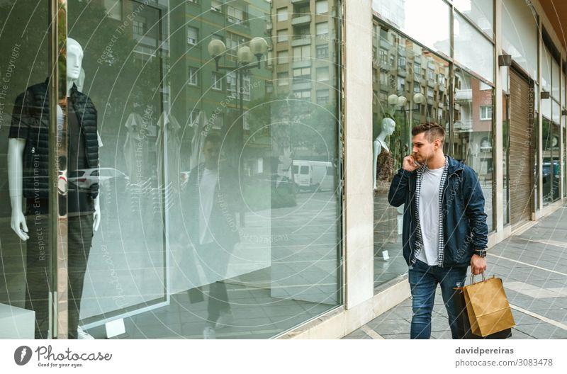 Mann mit Einkaufstaschen im vorderen Bekleidungsgeschäft Lifestyle kaufen Stil sprechen PDA Mensch Erwachsene Mode Jeanshose authentisch jung laufen Ladenfront