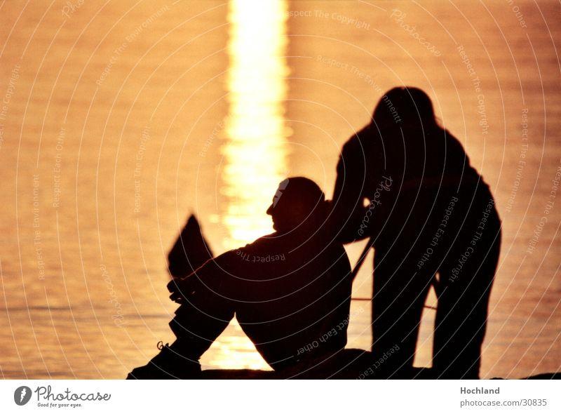 Schnürsenkel am Abend Frau Mann Wasser Sonne Paar sitzen Fotograf Abenddämmerung Schuhbänder