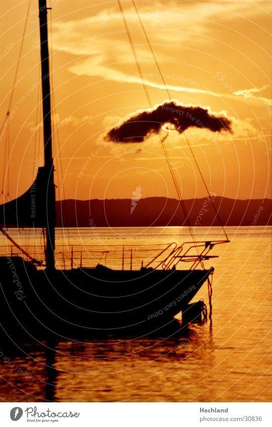 Segelboot im Abendlicht Wasser Sonne Wolken Strommast Abenddämmerung