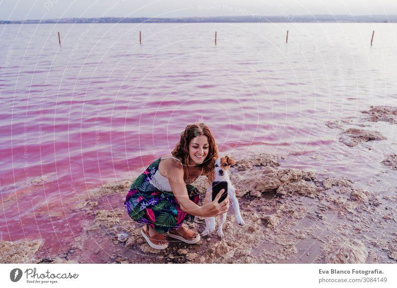 junge schöne Frau, die an einem rosa See mit Hund steht. Lifestyle Freude Glück Erholung Freizeit & Hobby Ferien & Urlaub & Reisen Tourismus Sommer Strand Meer