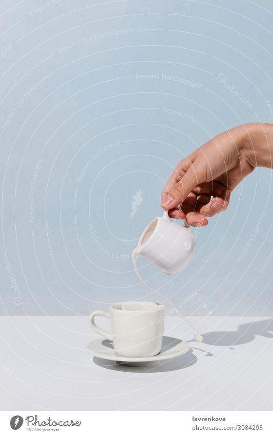 Frauenhand, die Mandelmilch in eine Tasse Kaffee gießt. aromatisch Getränk Frühstück Koffein Milchkännchen Hand heiß Lifestyle Morgen Becher eingießen