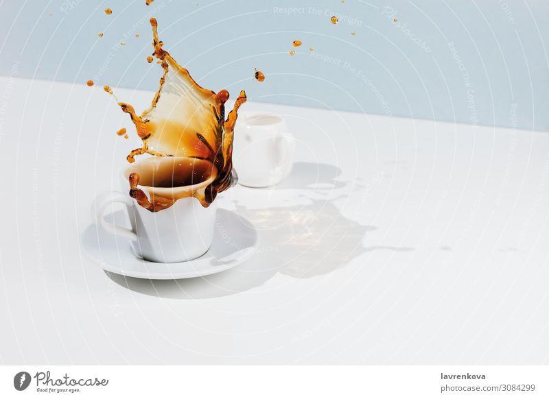Nahaufnahme der Tasse mit spritzendem Kaffee, Untertasse und Milchkännchen Pastellton blau Bewegung Tee Lebensmittel Foodfotografie Frühstück schwarz Tropfen