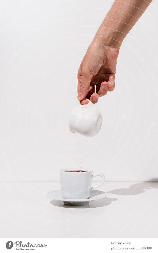 Frauenhand, die Mandelmilch in eine Tasse Kaffee gießt. Getränk Frühstück Koffein Keramik Milchkännchen frisch Hand heiß Morgen Becher Untertasse Tee weiß