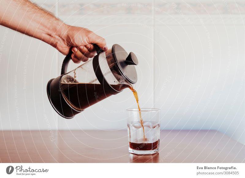 kaukasischer Mann, der Kaffee in einem transparenten Glas serviert. Frühstück Getränk Geschirr Löffel Lifestyle kaufen Erholung Freizeit & Hobby Haus Tisch