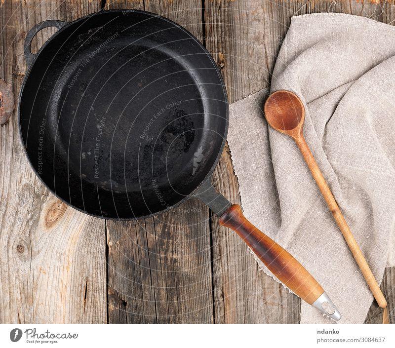leere schwarze runde Bratpfanne mit Griff und Löffel Pfanne Tisch Küche Werkzeug Holz Metall alt oben Sauberkeit braun grau Hintergrund Holzplatte gießen