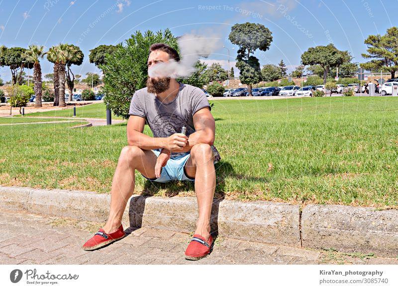 Viper Kaukasischer erwachsener bärtiger Hipster sitzt auf Gras und genießt das Wetter im Park Vollbart Erwachsener Mann Kaukasier männlich Porträt jung Mode