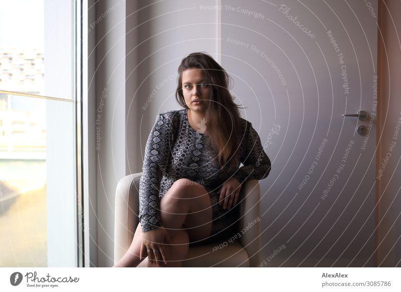 Portrait einer jungen Frau im Sessel Jugendliche Junge Frau Stadt schön Fenster 18-30 Jahre Lifestyle Erwachsene Leben sprechen feminin Stil Raum elegant