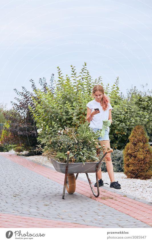 Teenager-Mädchen bei der Arbeit in einem Hausgarten Lifestyle Glück Freizeit & Hobby Sommer Garten Arbeit & Erwerbstätigkeit Gartenarbeit Telefon Handy PDA