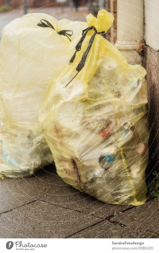 Two yellow rubbish bags on the street Arbeit & Erwerbstätigkeit Dienstleistungsgewerbe Umwelt Stadt Haus trashig gelb dirty waste plastic garbage collection