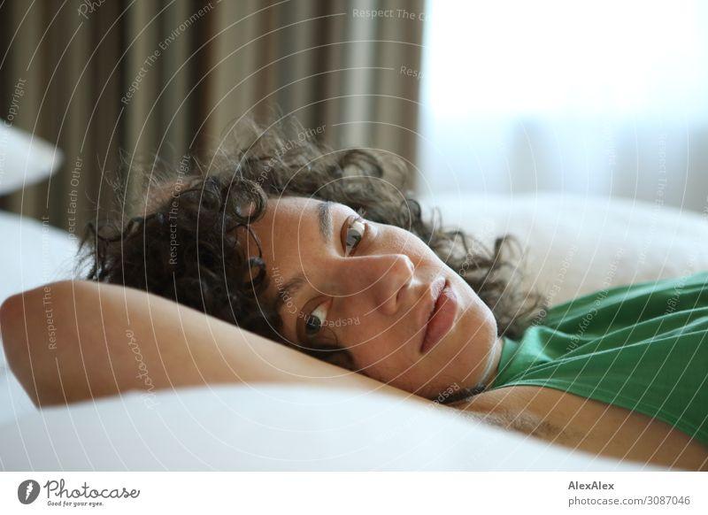 Portrait einer jungen Frau Junge Frau Jugendliche Gesicht 18-30 Jahre Erwachsene T-Shirt schwarzhaarig langhaarig Locken Bett Raum liegen Blick ästhetisch