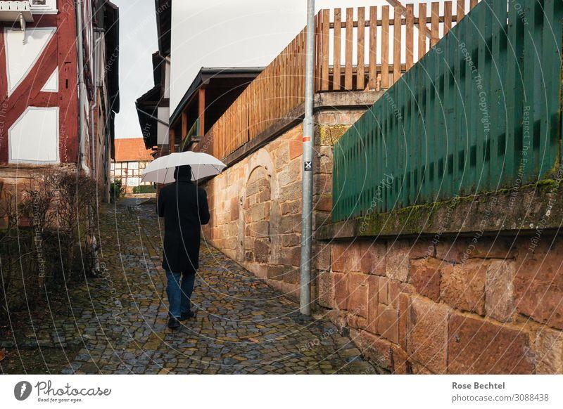 Mann mit Schirm ruhig maskulin Erwachsene 1 Mensch Dorf Fußgänger Wege & Pfade Mode Jeanshose Mantel Regenschirm Mütze Stein Bewegung Erholung gehen historisch
