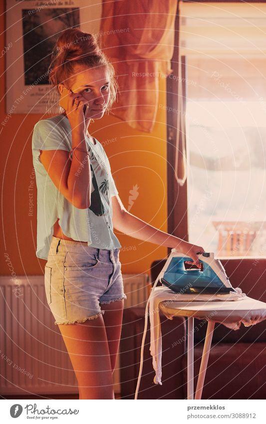 Junge Frau bügelt ihre Kleider und spricht auf einem Smartphone. Lifestyle Freude Glück schön Haus sprechen Telefon PDA Technik & Technologie Mensch Jugendliche